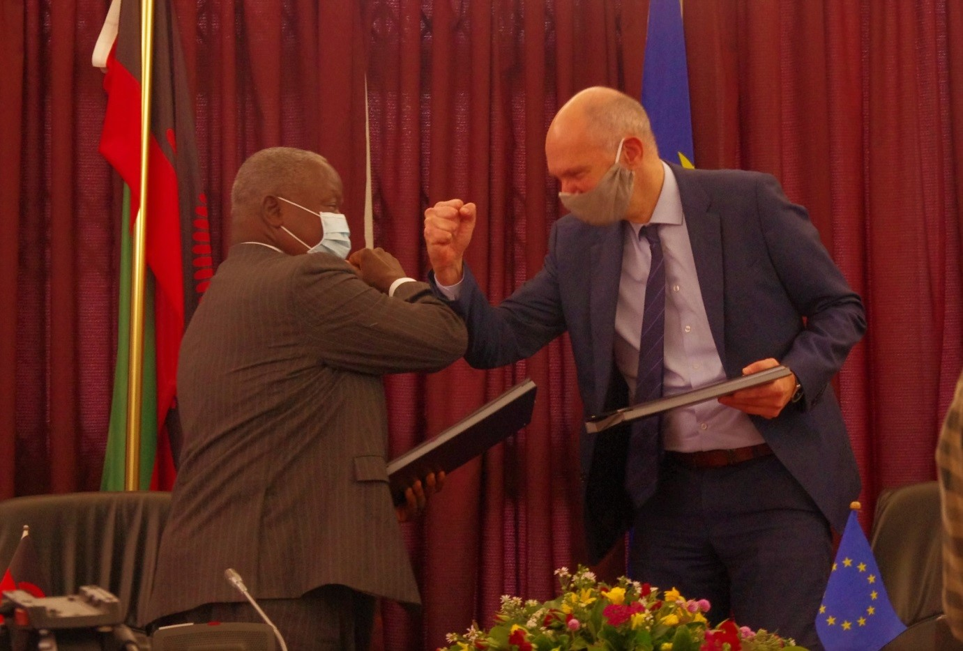 Hon. Felix Mlusu, Minister of Finance and Ivo Hoefkens, EU Head of Cooperation and Charge d'Affaires confidently exchanging signed documents on the Zantchito (Skills for Jobs) Programme